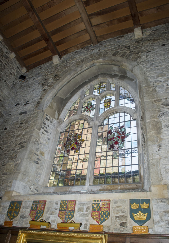 The chapel's East Window with the crests of de Cobham and Knolles. The glass for the windows was installed in 1937. Above these crests are the coat of arms of the See of Rochester and the City of Rochester. The seven shields beneath the window were previously on the exterior of the building above the doorway to the 18th century porch.