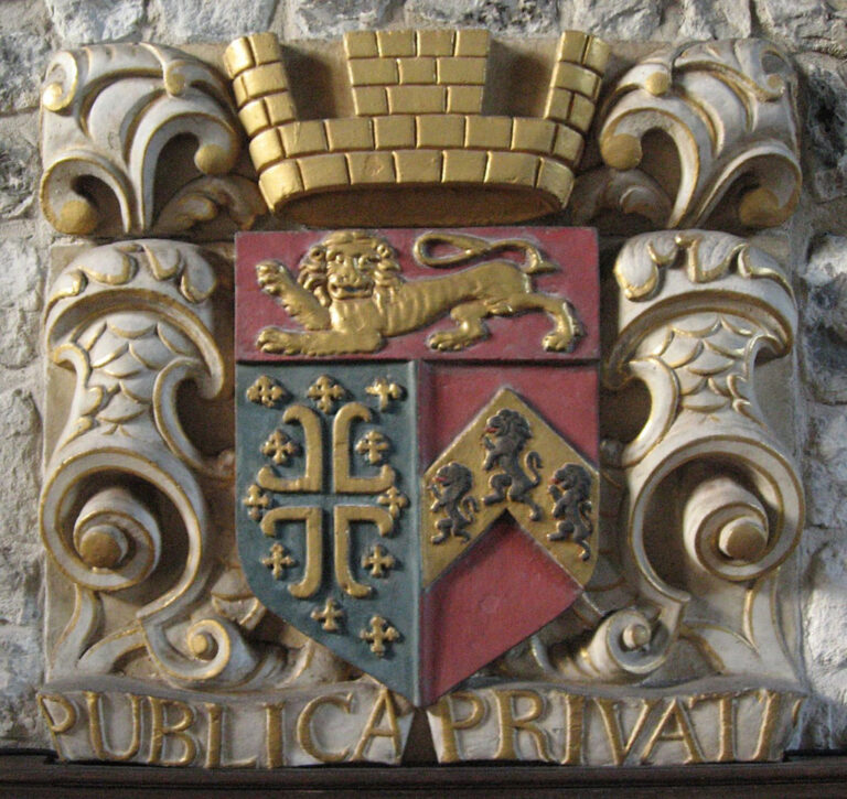 Coat of arms and plaque (which refers to the storage of the records) originally on the front of the 18th century porch. (This plaque is now found on the internal chapel wall, it confirms that the additional frontage was built by the Wardens for the storage of the muniments in 1735.)