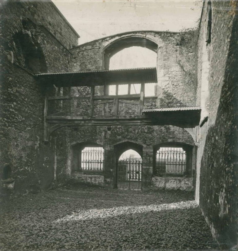 Photograph of the remains of the chapel as they appeared in 1928. Note the ivy growing where the floor tiles had been.